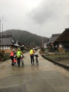 土砂降りの中自転車を押し歩く大内宿