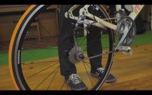 右手で後輪を地面に着けたまま抑え、左手でサドルの後ろを持ち、20cmくらい上方に引く