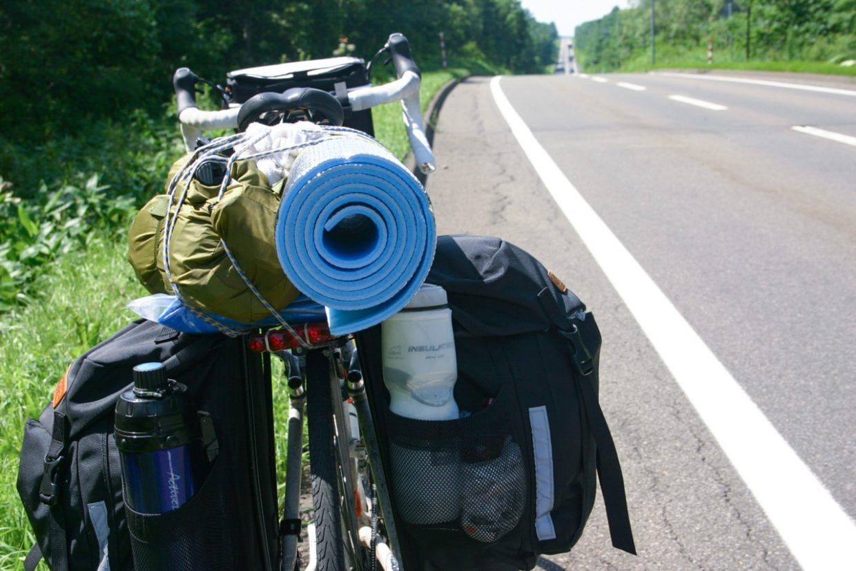北海道ツーリング中の一枚。バイクパッキングとは正反対のどっしり感。積載量と安定感がものすごく、長期旅においてはやはり絶対的な信頼感があります。パニアバッグの後方にはボトルが左右に1本ずつ、またバッグの上にはモンベルのムーンライトテントとホームセンターで手に入れた銀マットを積んでいます。photo:神楽坂つむり