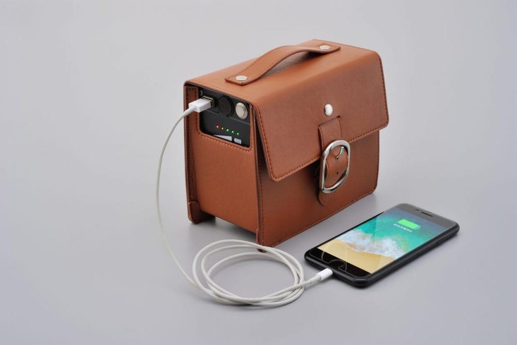 バッテリーはブラウンレザーバッグに内蔵。携帯電話等の充電が可能なUSB出力端子も装備。