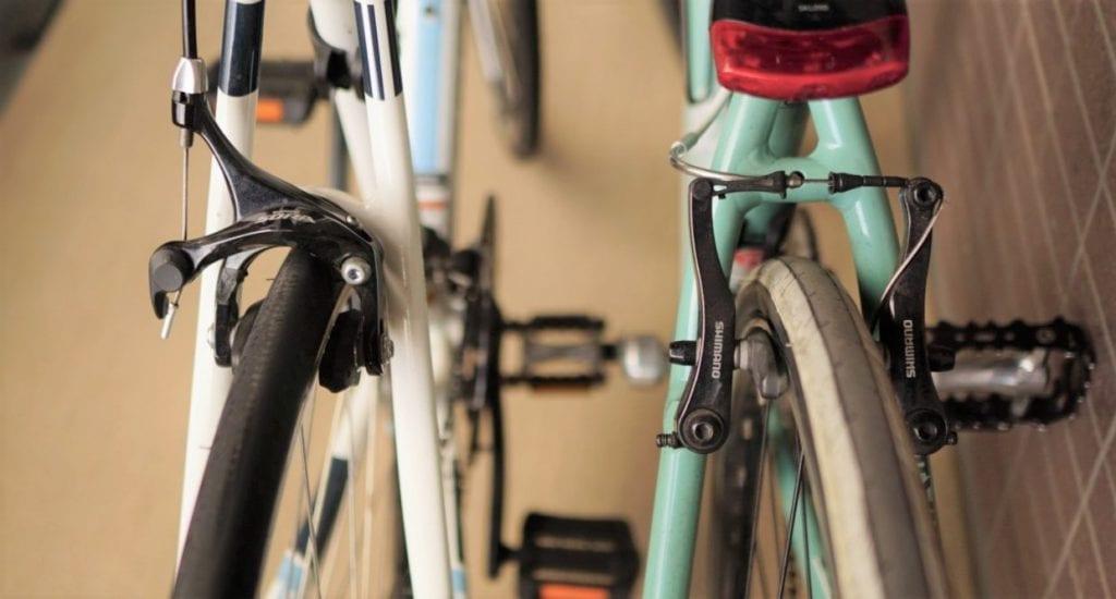 フラットバーロードのキャリパーブレーキ(左)と、クロスバイクのVブレーキ(右)