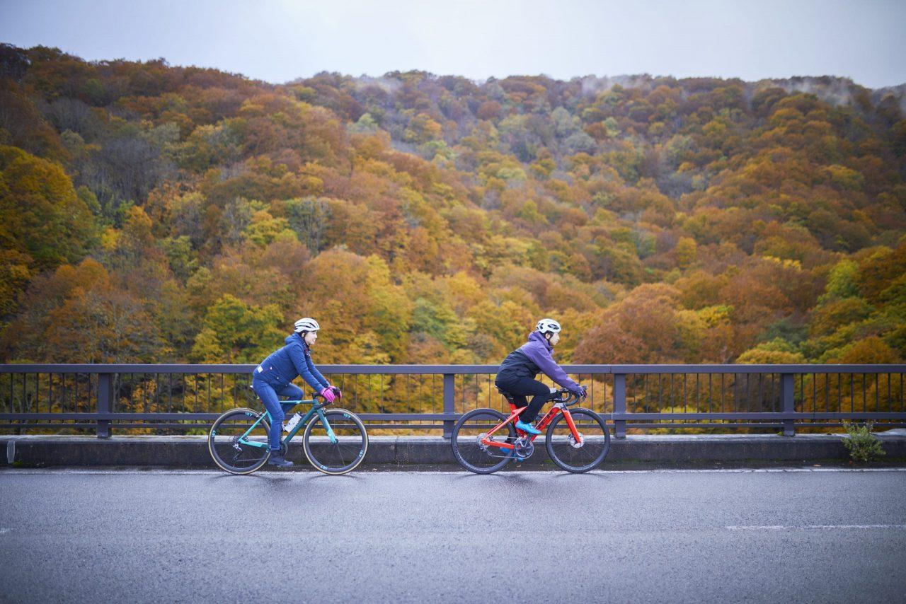 紅葉をバックに、桧原大橋をわたる